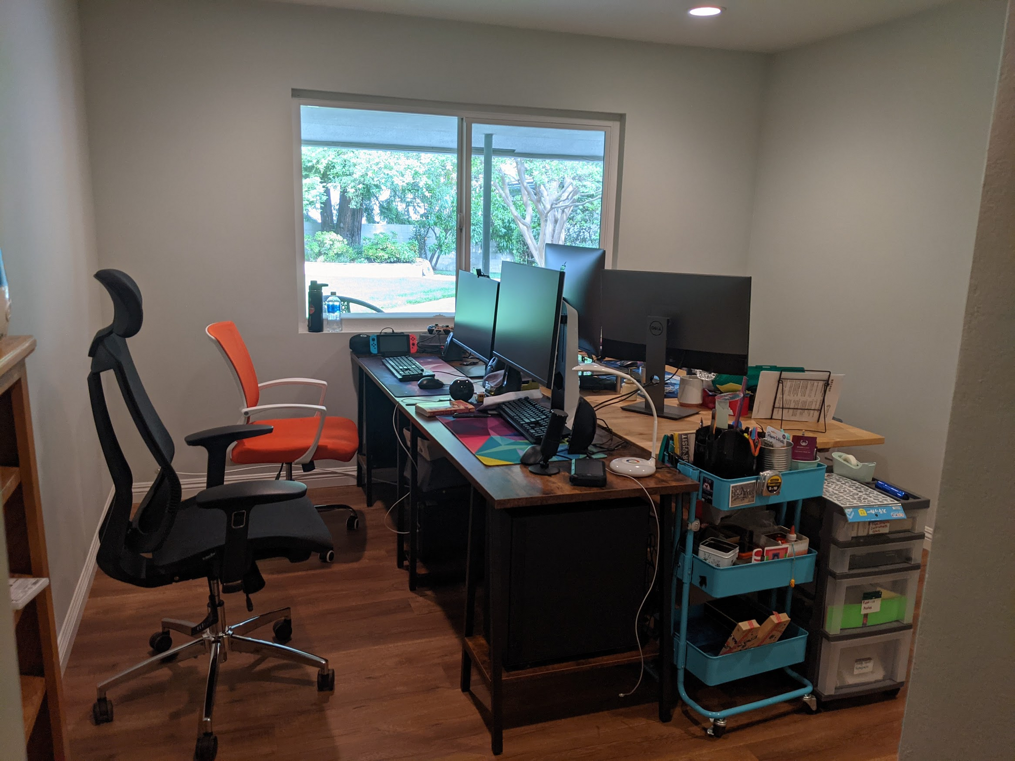 Computer desks across from each other with chairs and bench on either side